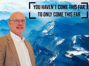 man with glasses overlaid on blue mountain background